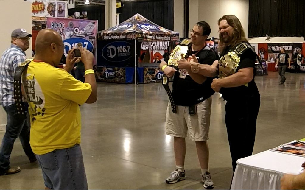Description of . Hall of Fame wrestler Hacksaw Jim Duggan (right) poses with a fan using his familiar thumbs up. Photo by David Komer