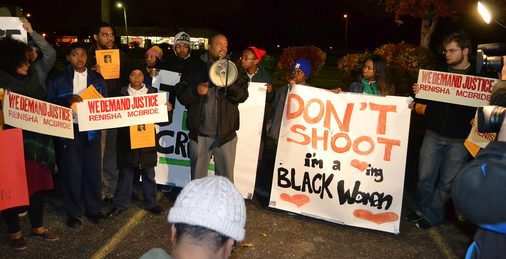 Description of . People took turns speaking to a crowd Thursday evening during a protest in front of the Dearborn Heights police station about the shooting death of young Detroit woman.