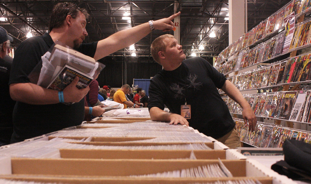 Description of . A man asks for a specific comic along the wall at the Motor City Comic Con. (Photo by Erica McClain)