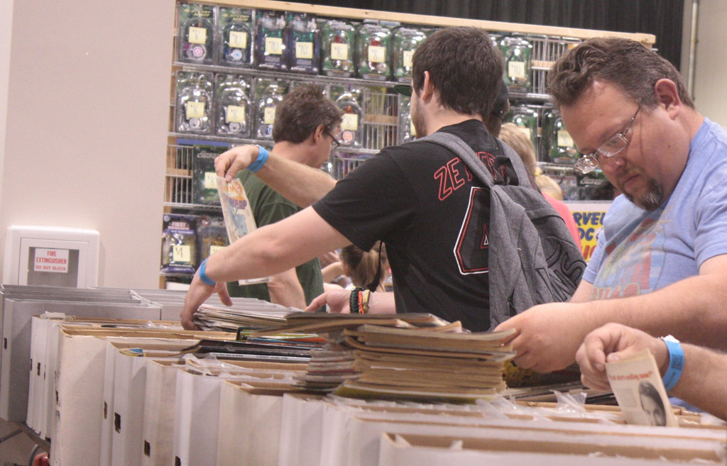 Description of . Fans search for elusive titles in the comic bins. (Photo by Erica McClain)