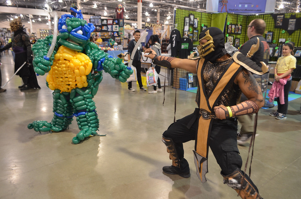 ". Cosplayers dressed as Leonardo the Ninja Turtle and Scorpion from the ""Mortal Kombat\"" video game franchise. Photo by Dave Herndon."