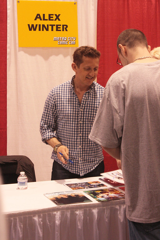 ". ""Bill & Ted\"" actor Alex Winter gets ready to sign a photo for a fan. (Photo by Erica McClain)"