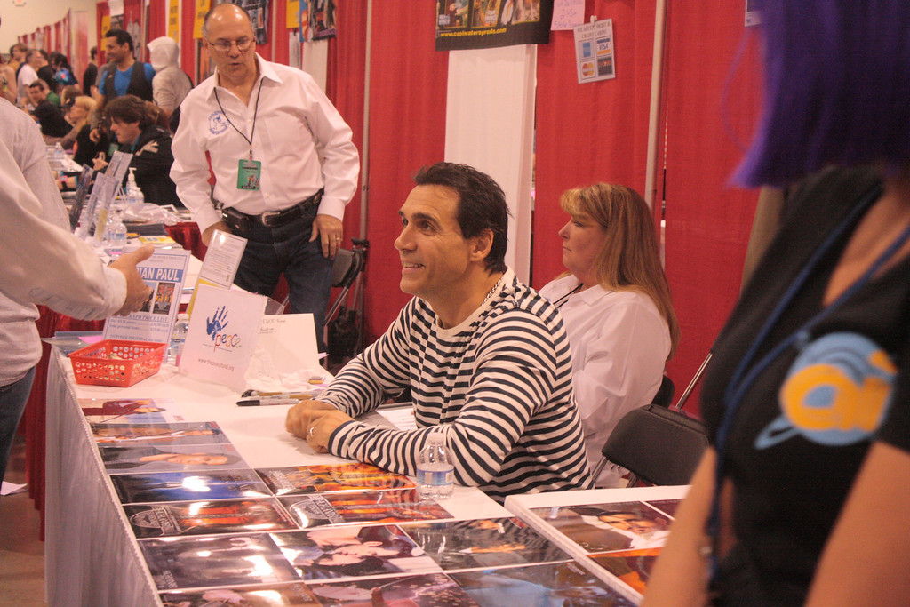 ". Actor Adrian Paul, known for his role Duncan McLeod in ""The Highlander,\"" greets a fan at the Motor City Comic Con on Saturday. (Photo by Erica McClain)"